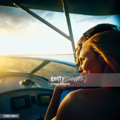Woman relaxing on man's shoulder on boat at low light : Stock Photo