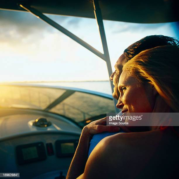 Woman relaxing on man's shoulder on boat at low light