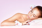 Portrait of a beautiful gentle woman with closed eyes relaxing on massage table in spa salon, healthy lifestyle, beauty treatment