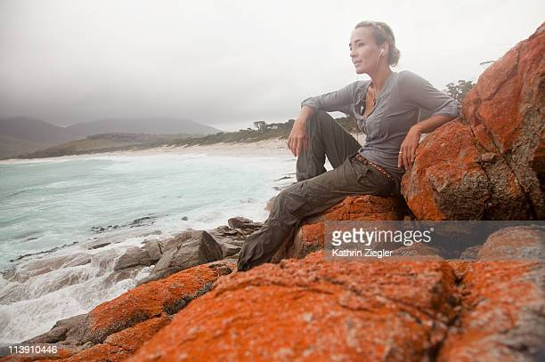 woman relaxing on orange algae rocks, Tasmania