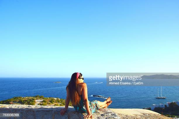 Woman Relaxing On Retaining Wall By Sea Against Sky On Sunny Day