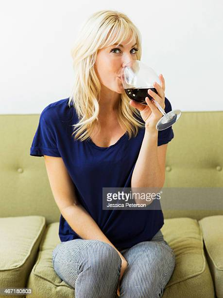 Woman relaxing on sofa and drinking wine