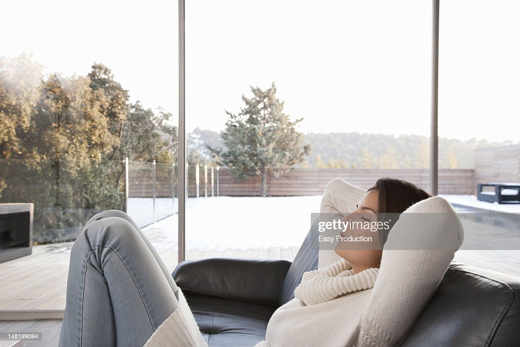Woman relaxing on sofa in living room : Stock Photo