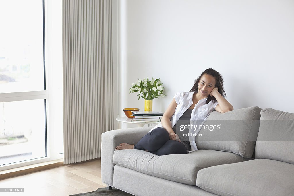 Woman relaxing on sofa in modern apartment, happy : Stock Photo