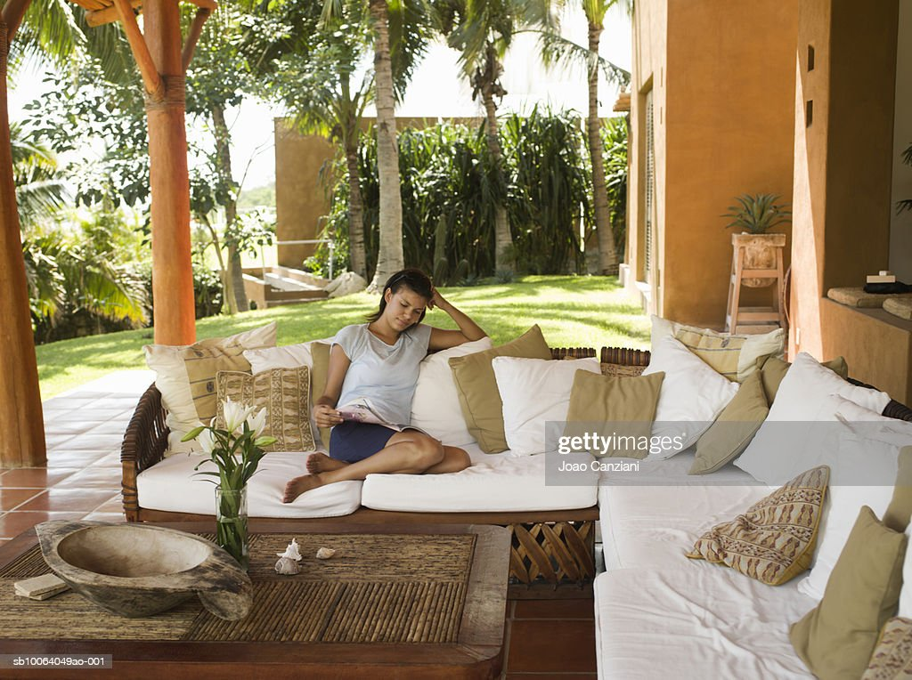 Woman relaxing on sofa on porch : Stock Photo