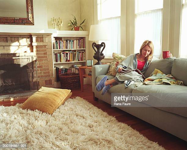 Woman relaxing on sofa, reading magazine