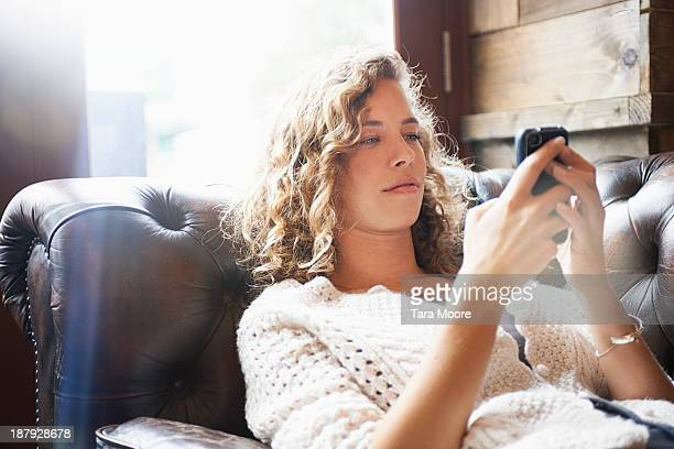 woman relaxing on sofa using mobile phone