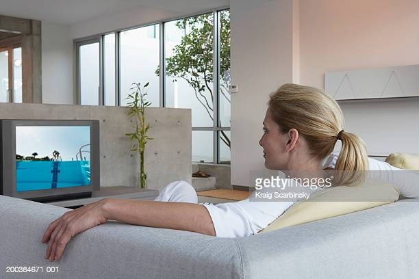Woman relaxing on sofa watching television, rear view