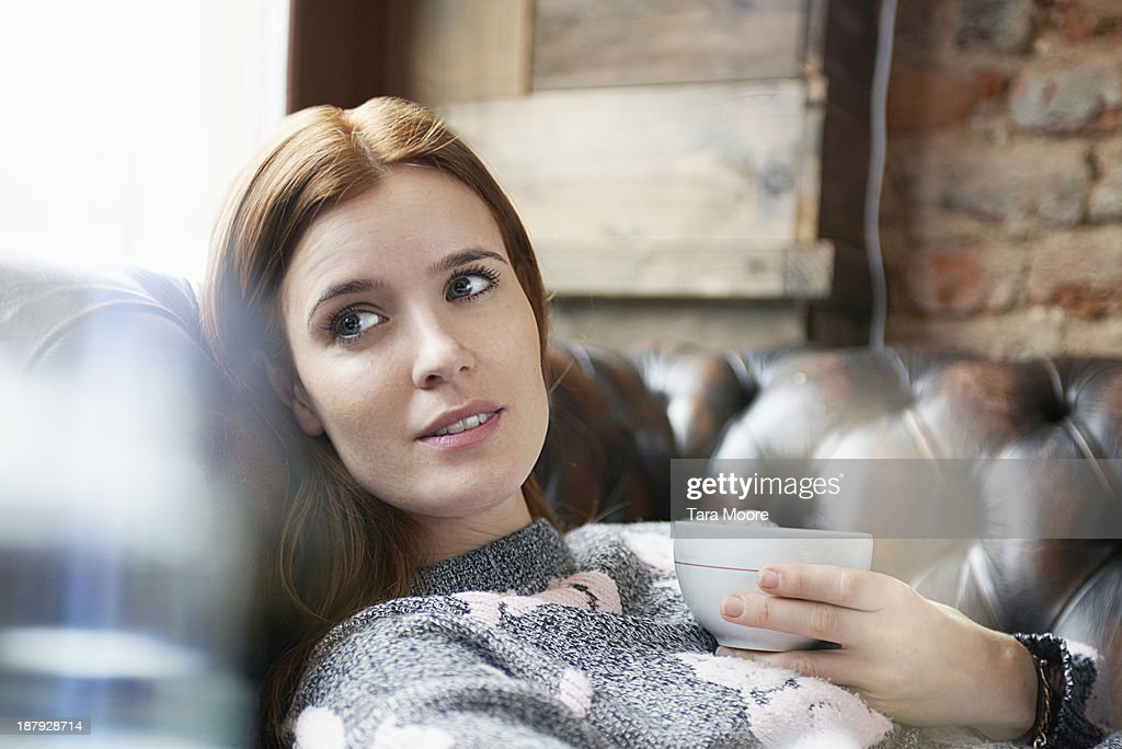 woman relaxing on sofa with coffee