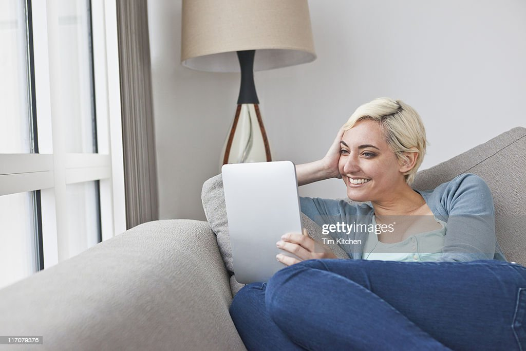 Woman relaxing on sofa with digital tablet : Stock Photo