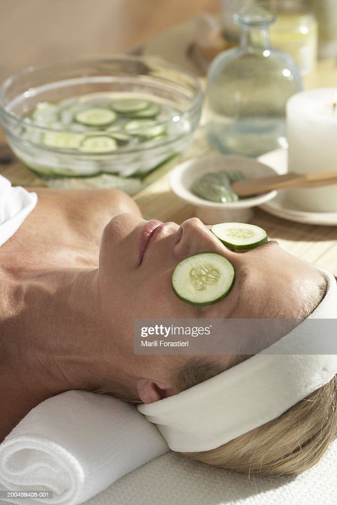 Woman relaxing on table with cucumber slices over eyes : Stock Photo