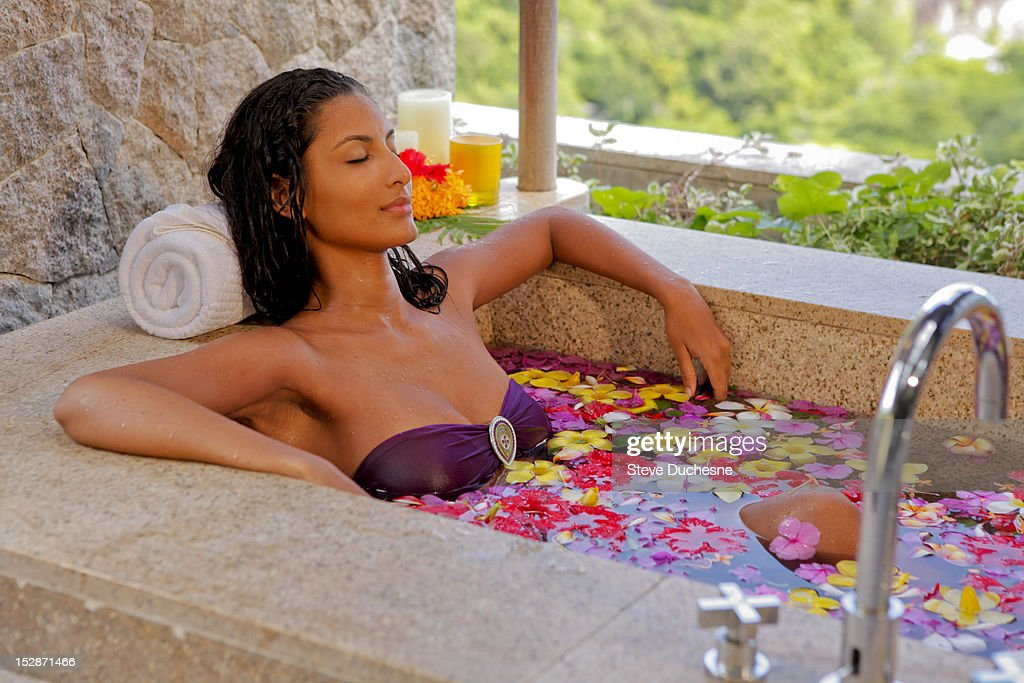 Woman relaxing on the bath with flowers : Stock Photo