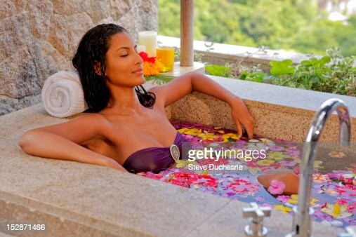 Woman relaxing on the bath with flowers : Stockfoto