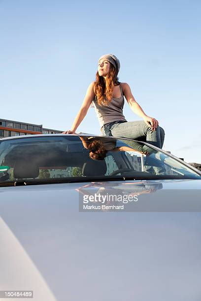 Woman relaxing on top of her car.
