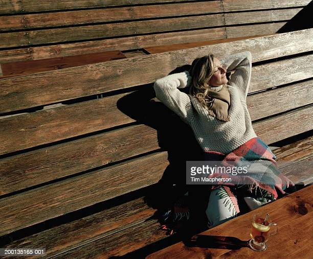 Woman relaxing on wooden bench by chalet, elevated view