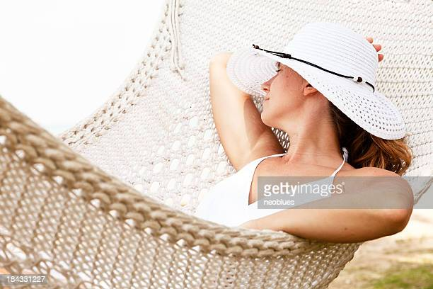 A woman relaxing outdoors on a hammock