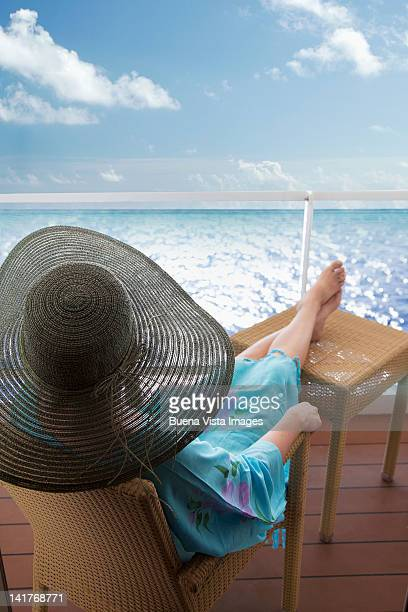 Woman relaxing outside her cabin on a cruise ship