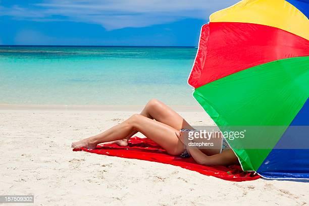 Frau entspannenden unter rainbow bunten Sonnenschirm am tropischen Strand
