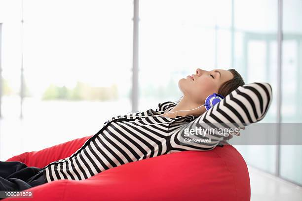 Woman relaxing while listening music through headphones