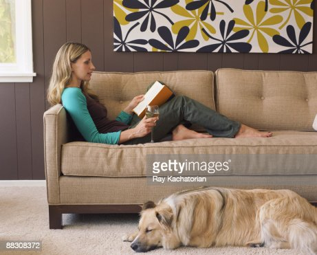 Woman relaxing with book and glass of wine in contemporary living room : Stock Photo