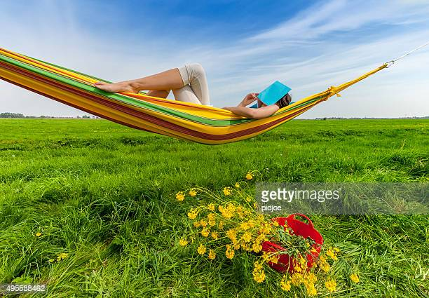 woman relaxing with book in hammock
