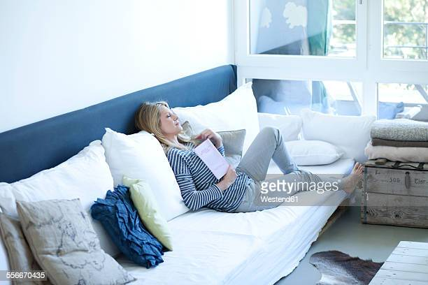 Woman relaxing with book on a couch