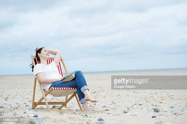Woman relaxing with book on deck chair.