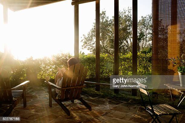 Woman relaxing with coffee and a book on veranda.