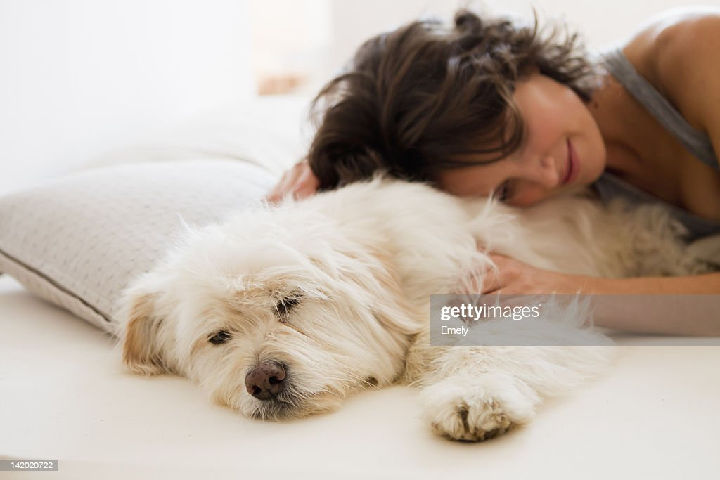 Woman relaxing with dog in bed : Stock Photo