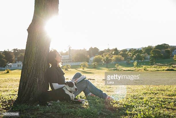 Woman relaxing with dog in park
