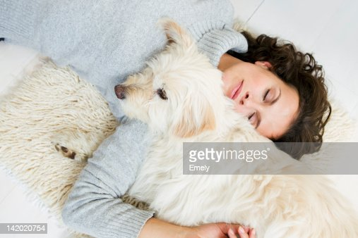 Woman relaxing with dog on rug : Stock Photo