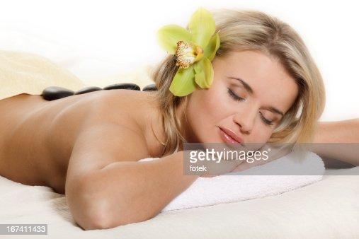 Frau entspannend mit Blumen und warmen Steinen : Stock-Foto