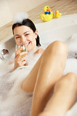 Woman Relaxing With Glass Of Wine In Bubble Filled Bath
