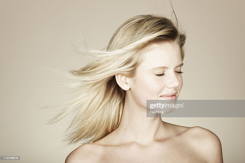 Woman relaxing with her hair blowing in the wind : Stock Photo