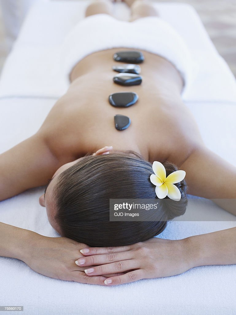 Woman relaxing with massage stones on her back : Stock Photo