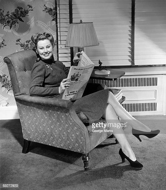 Woman relaxing w/newspaper at home