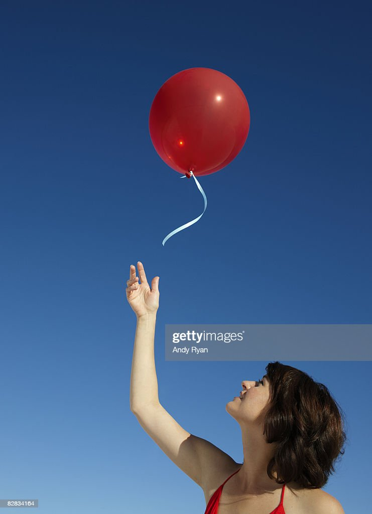 Woman Releasing Red Balloon : Stock Photo