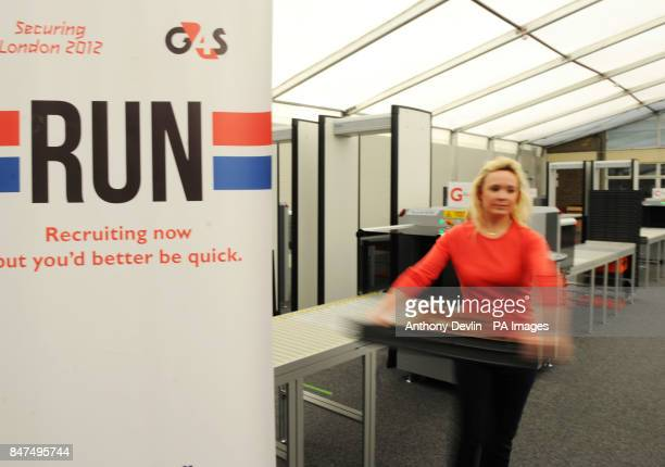 A woman removes a tray from an xray machine as Olympic Games security company G4S trains its new recruits for the London 2012 Olympic Games Straford...