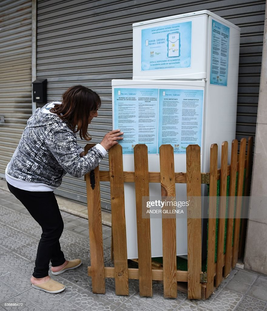 A woman removes food of the 'Solidarity Fridge' in the Spanish Basque city of Galdakao on May 30, 2016. An social initiative based on good will with the purpose to help feed the needy and reduce wastage. The 'refrigerator' project was launched by the Galdakao Humanitarian Volunteers Association on April 29, 2015 in a bid to give a second life to leftover food and food about to expire by placing a refrigerator in the street where neighbors and restaurants could deposit their surplus for people with limited resources to collect and use instead of dumping it. / AFP / ANDER