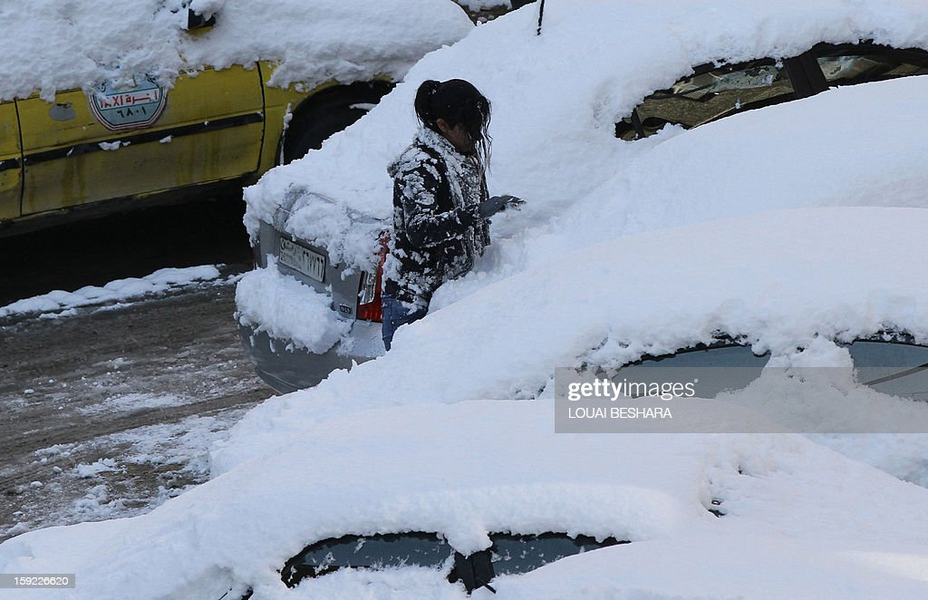 A woman removes snow from a car on January 10, 2013 in the Syrian capital of Damascus after heavy snow falls. Snow carpeted Syria's war-torn cities but sparked no let-up in the fighting, instead heaping fresh misery on a civilian population already enduring a chronic shortage of heating fuel and daily power cuts.