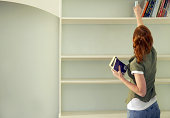 Frau entfernen Bücher im Regal