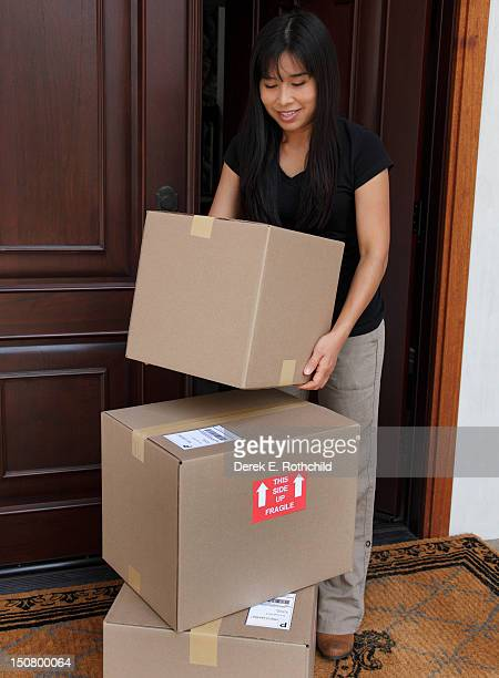 Woman removing box from stack at home