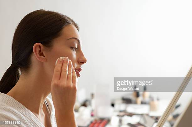 Woman removing make up with products in background