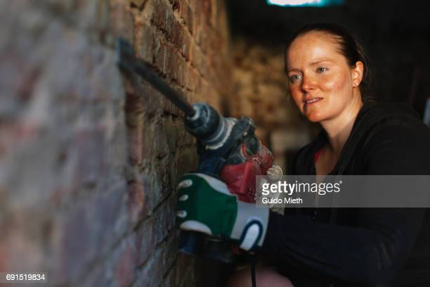 Woman removing old plastering.