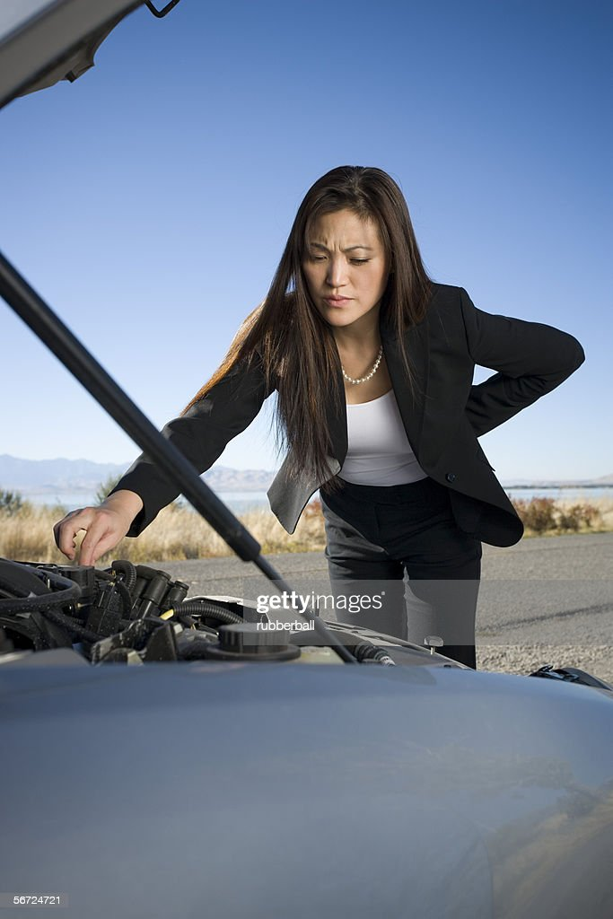 Woman repairing checking her car engine : Photo