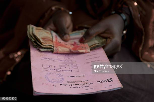 A woman repays her loan at a community microfinance meeting in Uganda Microfinance has become an important tool in developing countries by providing...