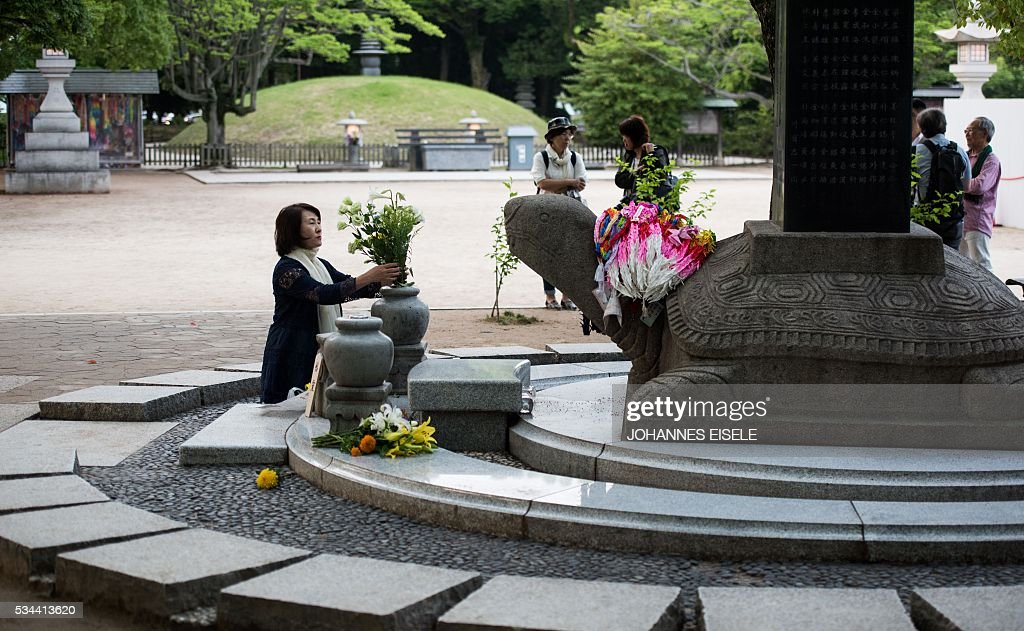 A woman replaces the flowers at the 'Monument in remembering of the Korean victims of A-bomb' in the Hiroshima Peace Memorial park in Hiroshima on May 26, 2016. US President Barack Obama is set to become the first sitting US president to visit one of the bomb sites when he journeys on May 27, 2016 with Japanese Prime Minister Shinzo Abe to Hiroshima, hallowed ground to Japanese but, for more than 70 years, a no-go zone for 11 of his Oval Office predecessors. / AFP / JOHANNES