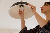 Woman replacing light bulb at home. Power save LED lamp changing