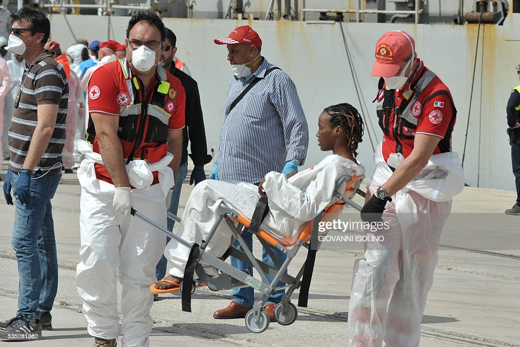 A woman rescued at sea receives medical assistance as the Italian Navy ship 'Vega' arrives with more than 600 migrants and refugees on May 29, 2016 in the port of Reggio Calabria, southern Italy. A week of shipwrecks and death in the Mediterranean culminated today with harrowing testimony from migrant survivors who said another 500 people including 40 children had drowned, bringing the number of feared dead to 700. / AFP / GIOVANNI