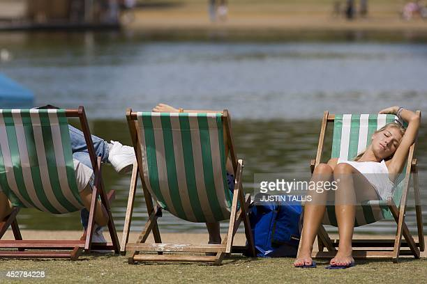 A woman rest on a deckchair by the Serpentine lake in Hyde Park central London as England basks in warm weather on July 27 2014 AFP PHOTO / JUSTIN...